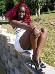 Black girl with bright red hair and in..